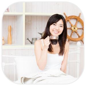 ベッドの上でコーヒを飲む白いワンピース姿の女性