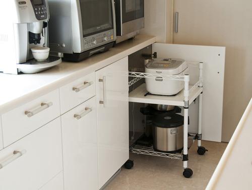 炊飯器を収納するオリジナル特注ワゴンと、オーブン&レンジをきれいに収納。作業がしやすいように高さ850mmに。引出しや扉の取っ手、収納スペースもご要望通りに。