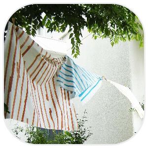 赤い縞模様と青い縞模様の洗濯物を干す