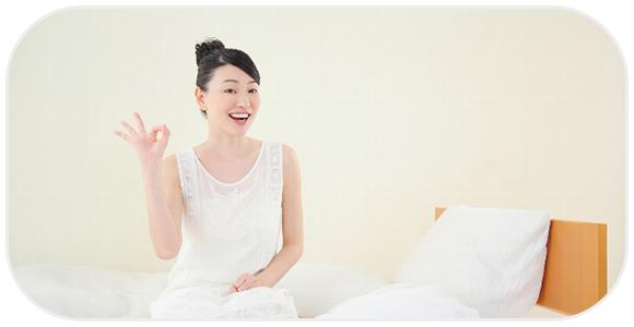 ベッドの上でokサインをする女性