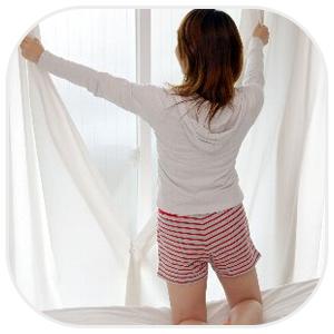 カーテンを開く女性