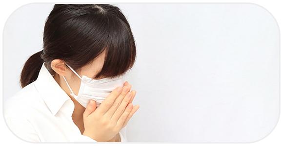マスクをして咳をする女性